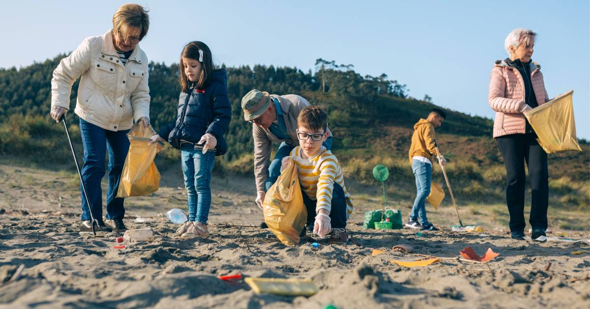 Older people and kids cleaning the beach together