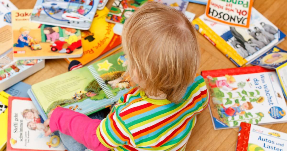 A toddler sat reading a book